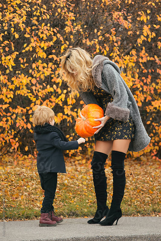 A mother holding out a pumpkin to her young curious son on a fall day by Ania Boniecka for Stocksy United