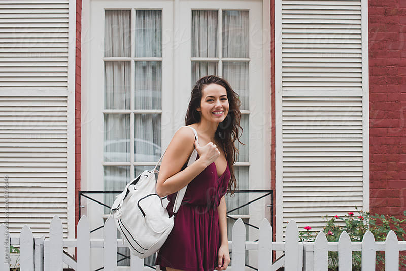 Happy young woman wearing backpack by Lauren Naefe for Stocksy United