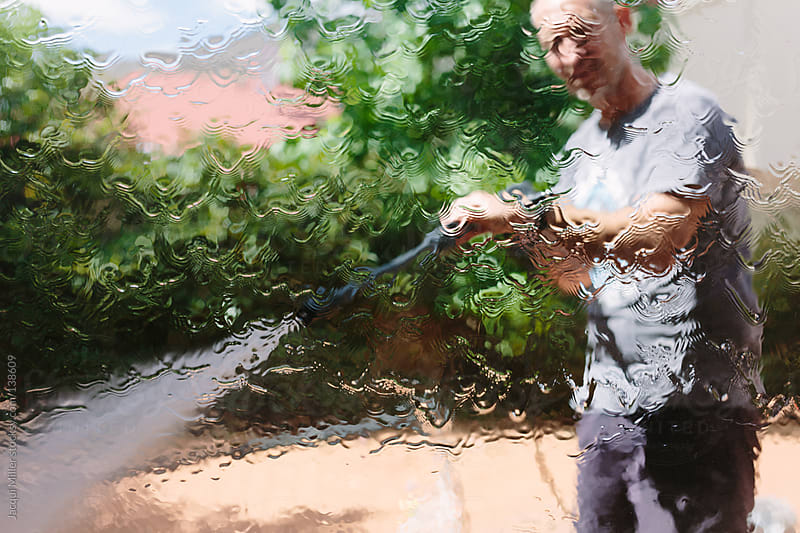 Man cleans windows with a high powered water pressure cleaner by Jacqui Miller for Stocksy United