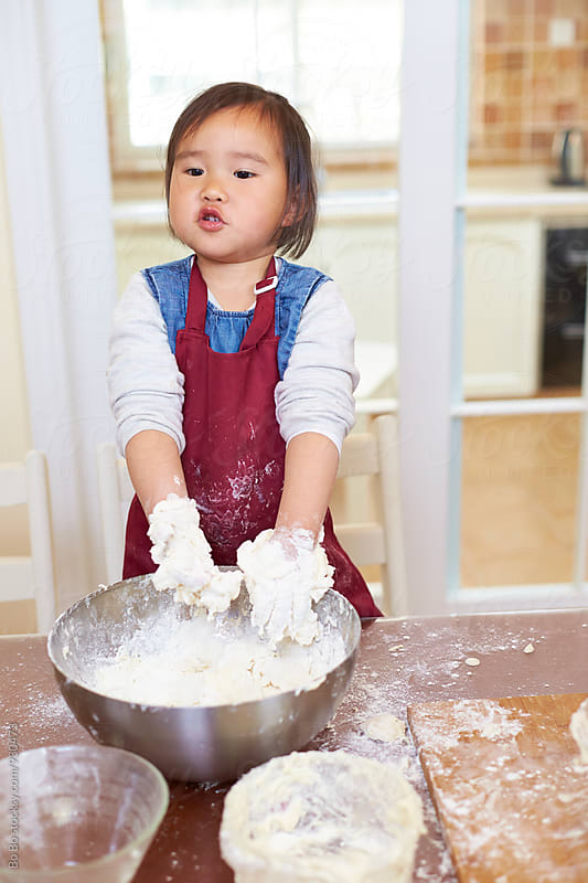 little asian girl mix flour in the bowl by Bo Bo for Stocksy United