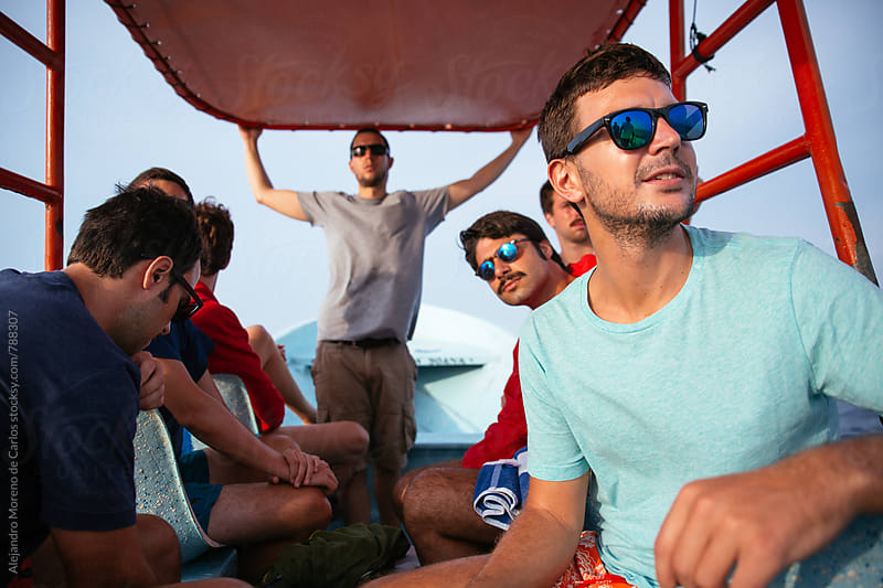 Young men doing a boat trip on a clear sky day by Alejandro Moreno de Carlos for Stocksy United