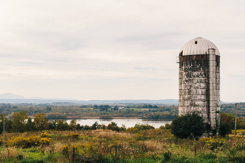 old grain silo overlooking a river by Deirdre Malfatto for Stocksy United