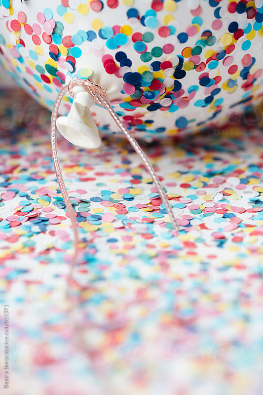 Closeup of a balloon covered with confetti by Beatrix Boros for Stocksy United
