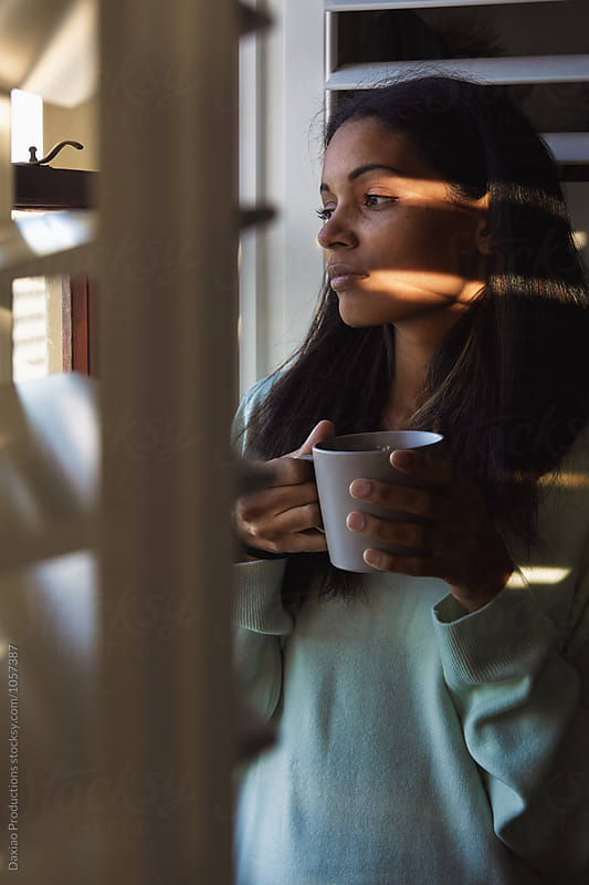 Woman with coffee at window blinds sunrise by Daxiao Productions for Stocksy United