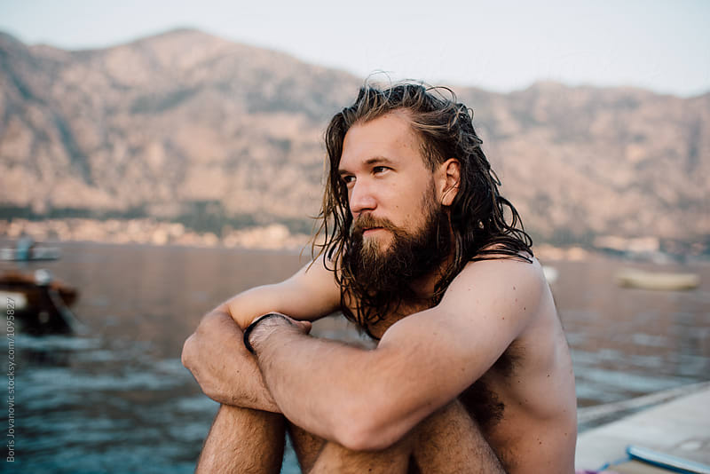 Young bearded man with long hair sitting near the sea by Boris Jovanovic for Stocksy United