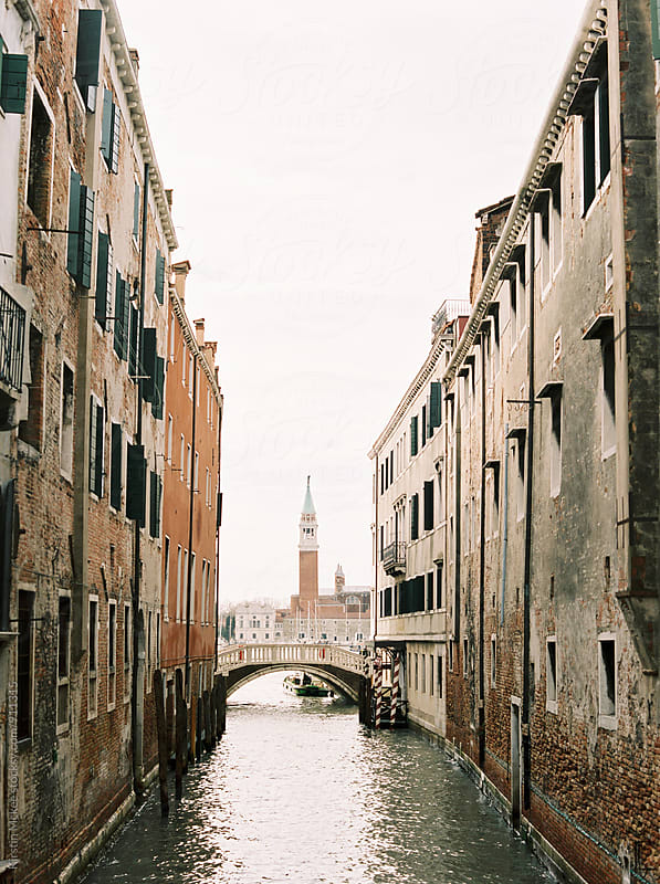 View of canal in Venice with tower by Kirstin Mckee for Stocksy United