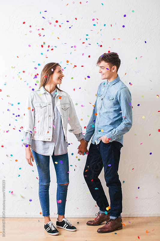 Young lovers holding hands as confetti falls from above. by BONNINSTUDIO for Stocksy United