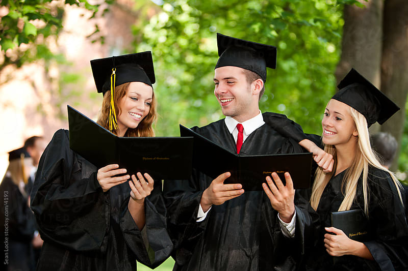 Graduation: Three Friends Looking at Graduation Diplomas by Sean Locke for Stocksy United