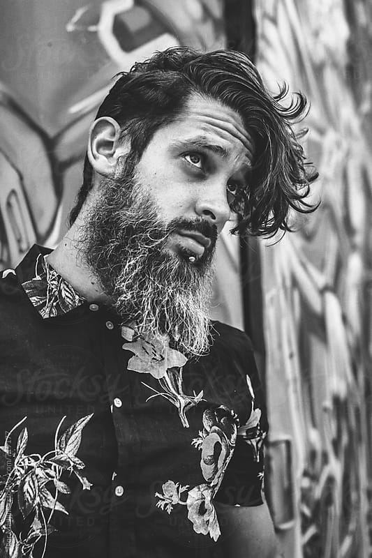 black and white portrait of a young hipster man in black shirt by Igor Madjinca for Stocksy United