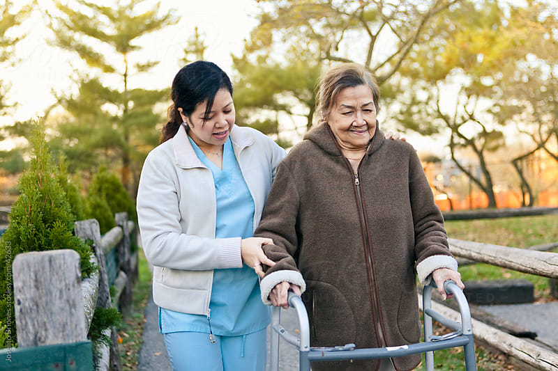 Homecare Nurse Helps Senior Citizen Patient Exercise by Joselito Briones for Stocksy United