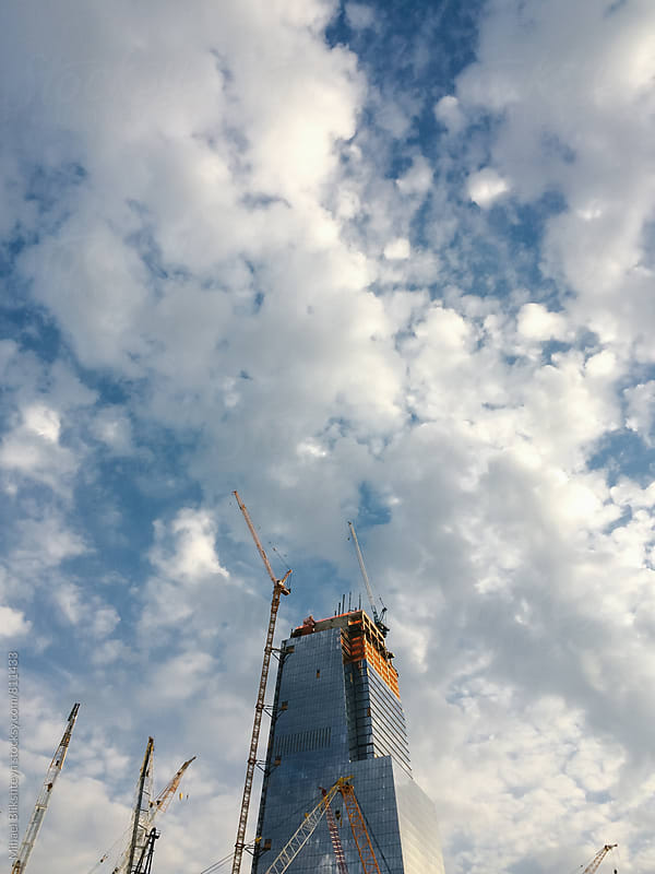 Construction of a skyscraper in a city with cranes against blue sky with clouds by Mihael Blikshteyn for Stocksy United
