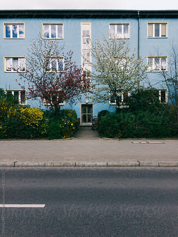 Blooming Trees In Front Of Blue Retro Apartment Building By VISUALSPECTRUM For Stocksy United