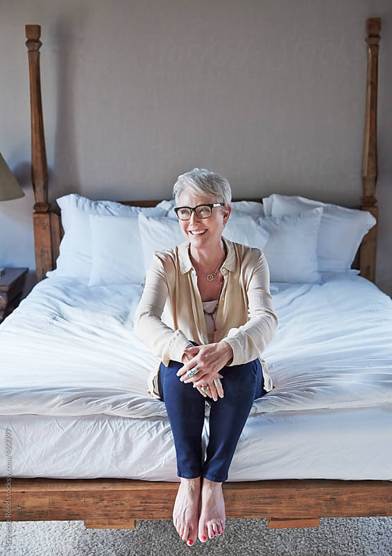 Portrait of mature woman with grey hair relaxing in bedroom by Trinette Reed for Stocksy United