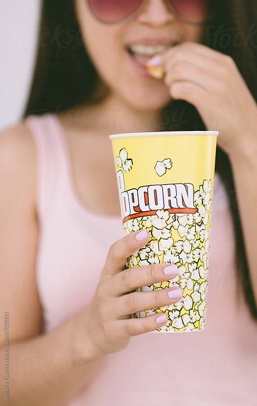 young asian woman  with popcorn by Vesna for Stocksy United