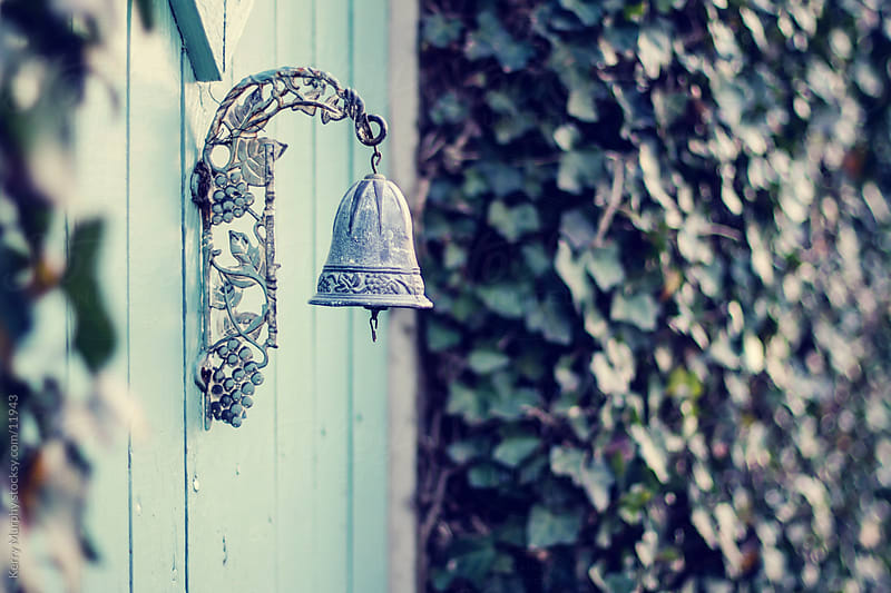 Bell hanging on fence with ivy by Kerry Murphy for Stocksy United