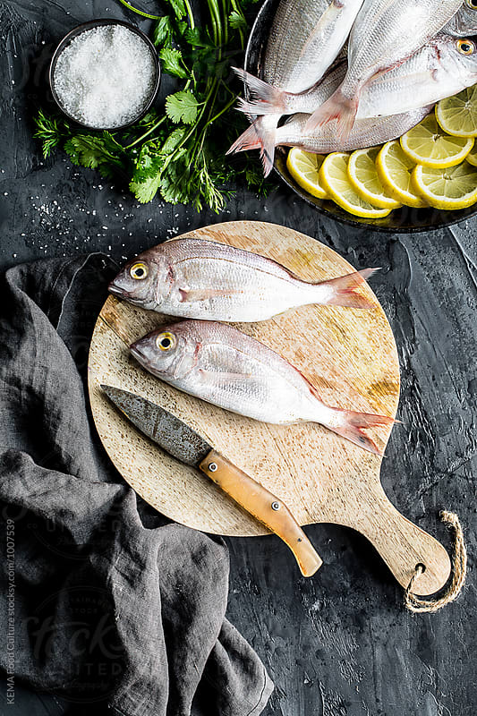 Sea bream on a cutboard with some ingredients by KEMA Food Culture for Stocksy United