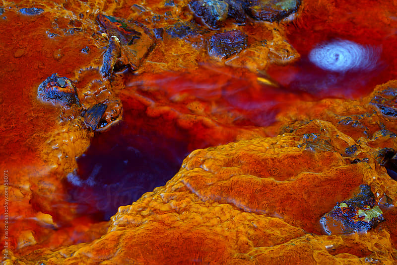 Aerial shot oxidised old mining iron minerals in water Rio Tinto by Marilar Irastorza for Stocksy United