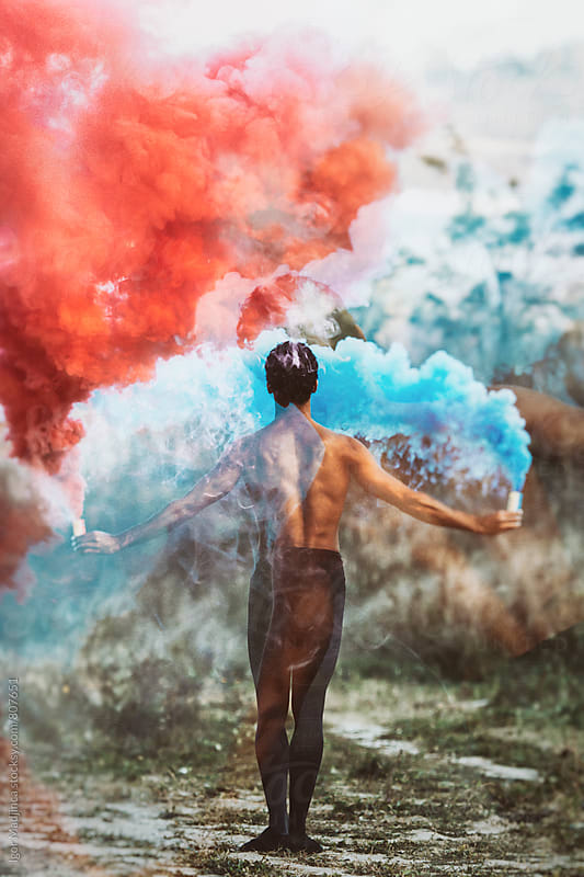 double exposure,from behind,ballet dancer with two colorful smoke bombs dance in nature by Igor Madjinca for Stocksy United