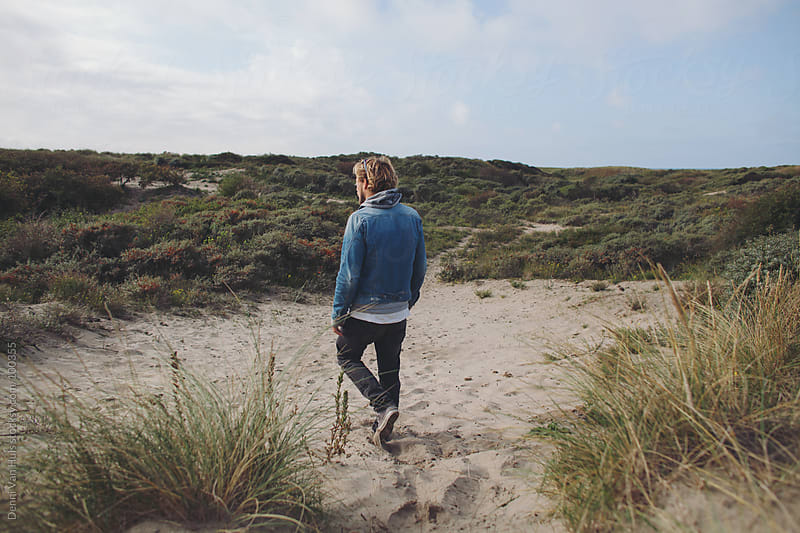 man walks on sand in the dunes by Denni Van Huis for Stocksy United