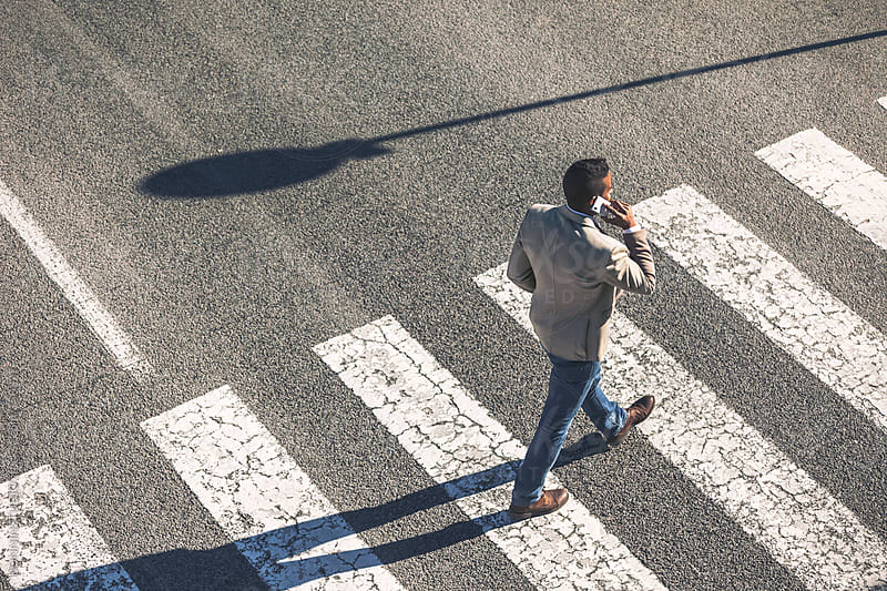 Back view of black businessman walking and talking with cell phone on a city crosswalk. by BONNINSTUDIO for Stocksy United