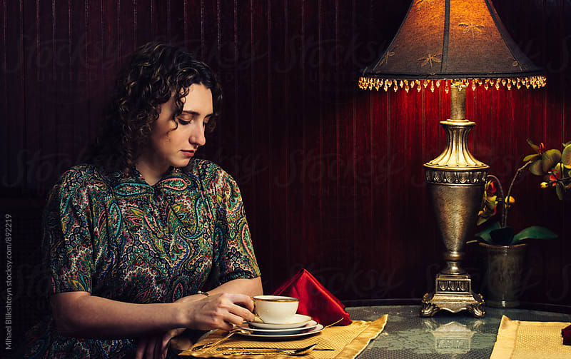 A 1950s period portait of a young sophisticated woman drinking tea in a cafe by Mihael Blikshteyn for Stocksy United