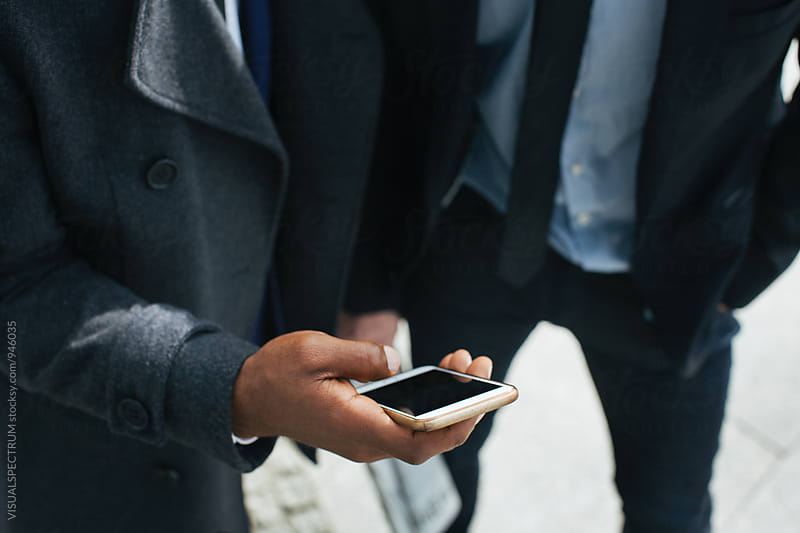 Closeup of Black Businessman Holding Smartphone in Hand by Julien L. Balmer for Stocksy United