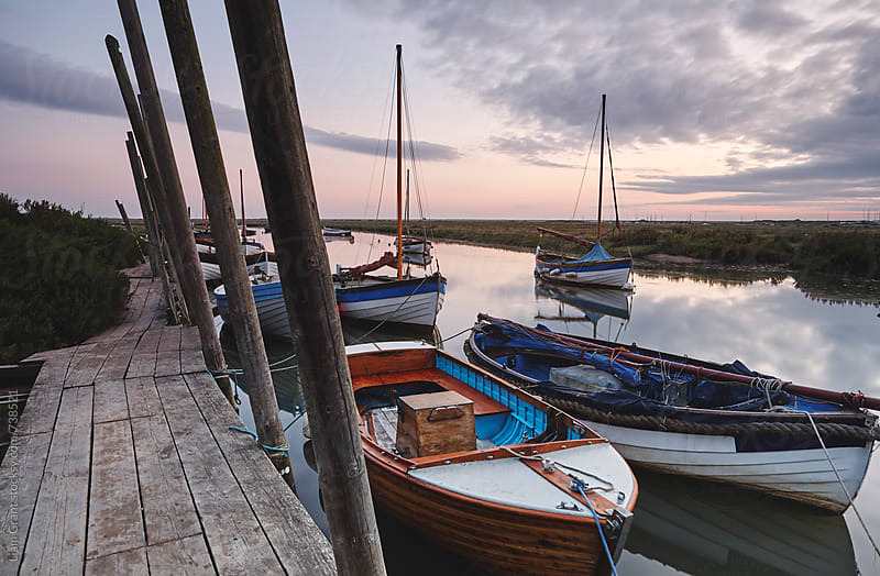 Boats moored in Blakeney Harbour at dawn. Norfolk, UK. by Liam Grant for Stocksy United
