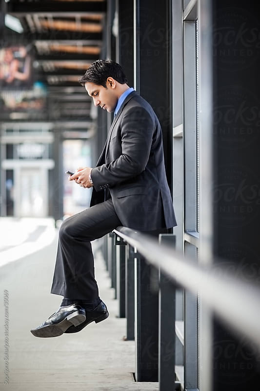 Indian businessman texting and checking his phone by Suprijono Suharjoto for Stocksy United