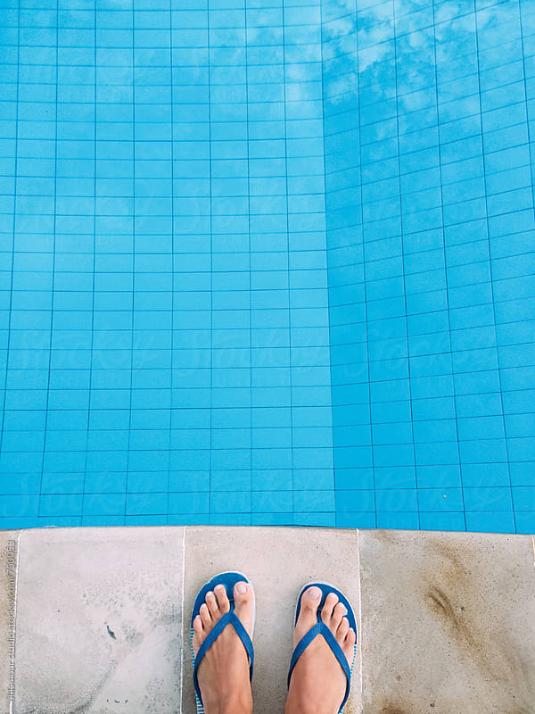Feet seen from above over the edge of a swimming pool by Leandro Crespi for Stocksy United