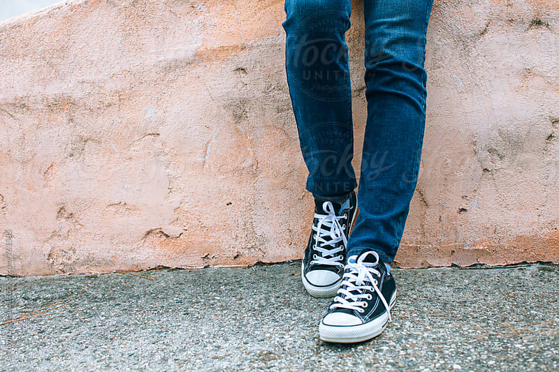 Teenager in jeans and sneakers standing against a wall by Carolyn Lagattuta for Stocksy United