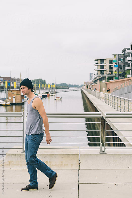 Man in tanktop at Waterfront  by Urs Siedentop & Co for Stocksy United