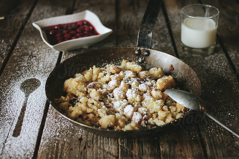 baked semolina porridge in a cast iron pan served with stewed cherries and milk on wooden board by Leander Nardin for Stocksy United