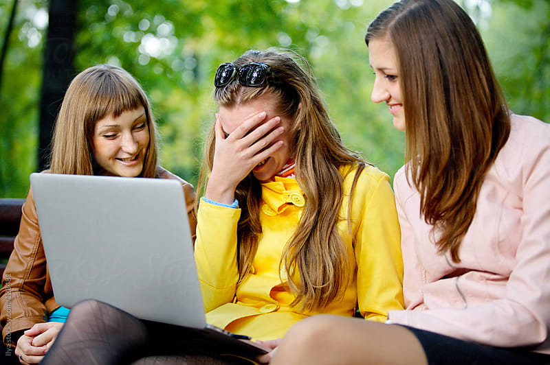 Young women friends sitting with laptop on park bench by Ilya for Stocksy United