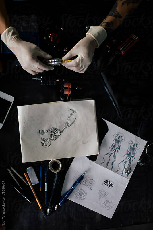 Tattoo artist table from above with sketchbook and tools by Nabi Tang for Stocksy United