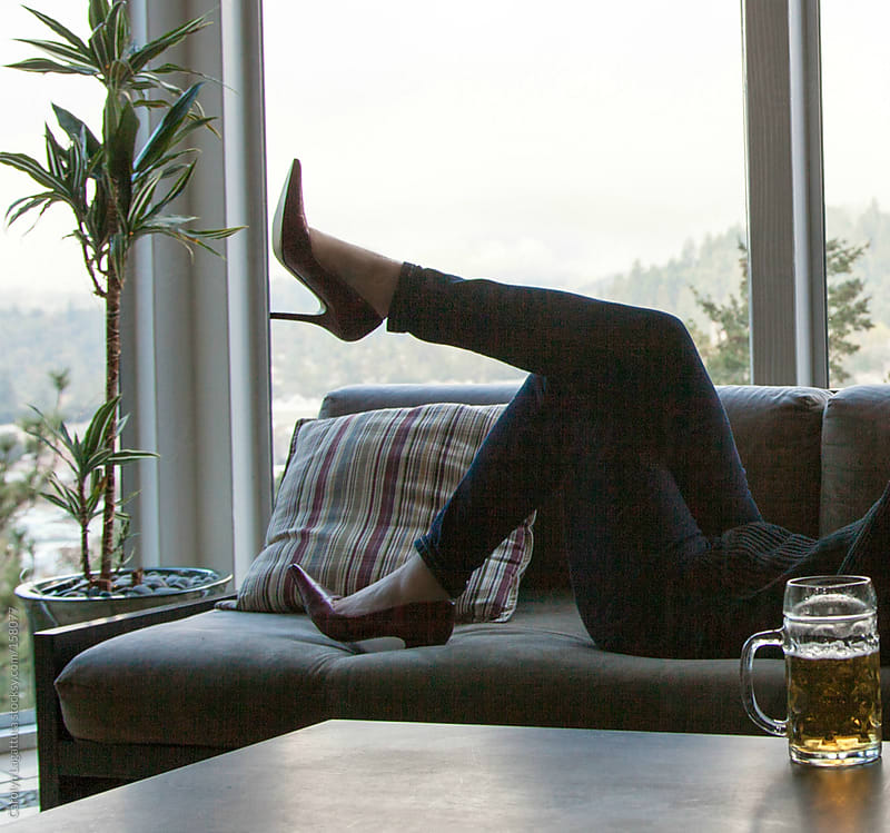 Woman laying on the couch in jeans and red heels - cold beer on the table by Carolyn Lagattuta for Stocksy United