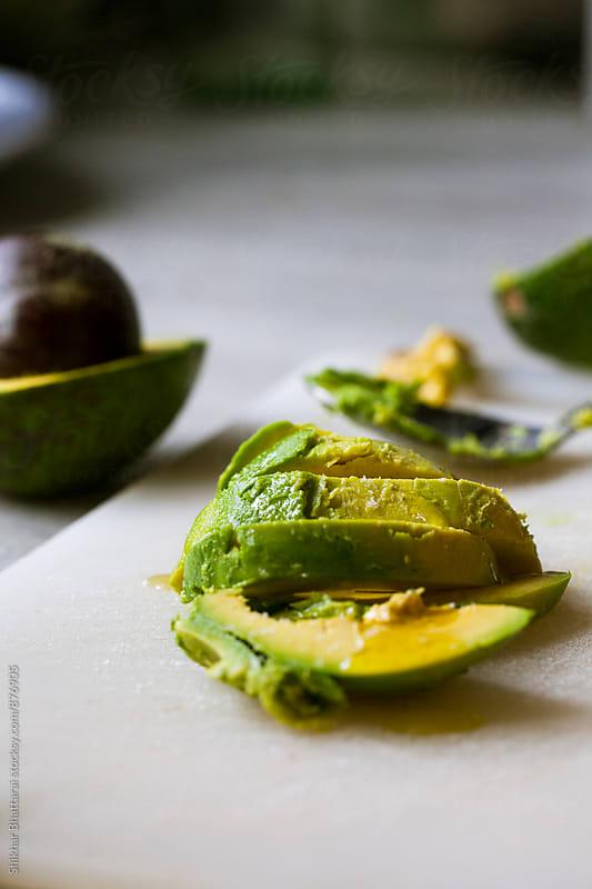 Sliced avocado on a chopping board. by Shikhar Bhattarai for Stocksy United