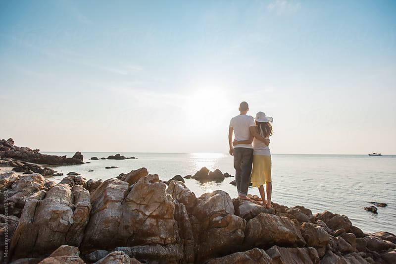 Couple Enjoying Sunset on a Rocky Beach by Mosuno for Stocksy United