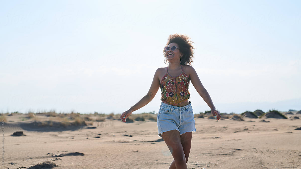 laughing woman with afro on beach in sunlight stocksy united