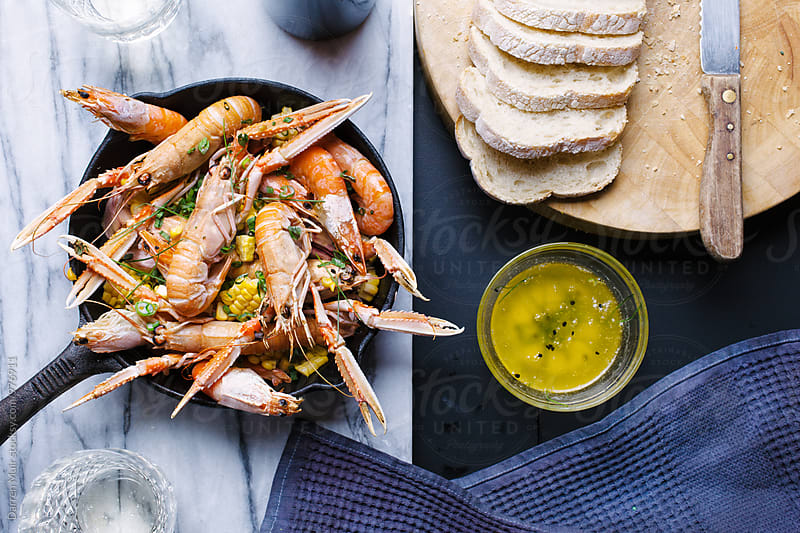 Roasted seafood in a skillet with corn and garlic butter. by Darren Muir for Stocksy United