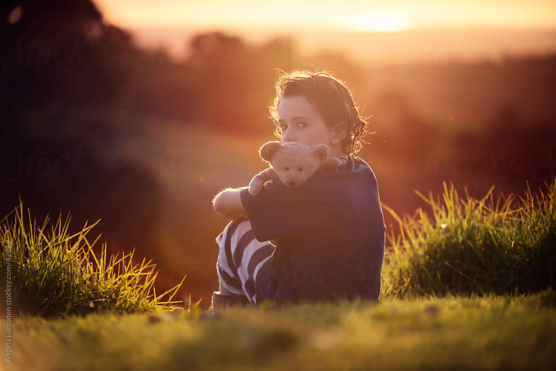 Young boy sitting with his teddy bear in the country at sunset by Angela Lumsden for Stocksy United