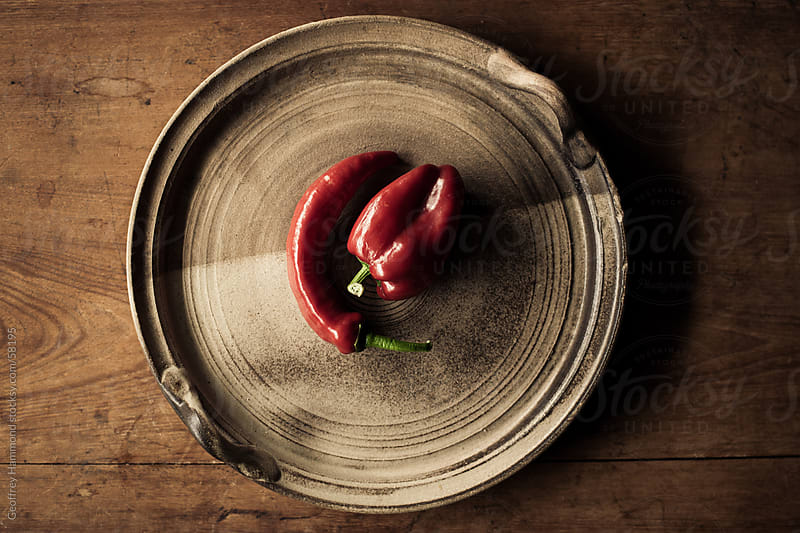 Two Red Peppers on Rustic Ceramic Plate by Geoffrey Hammond for Stocksy United