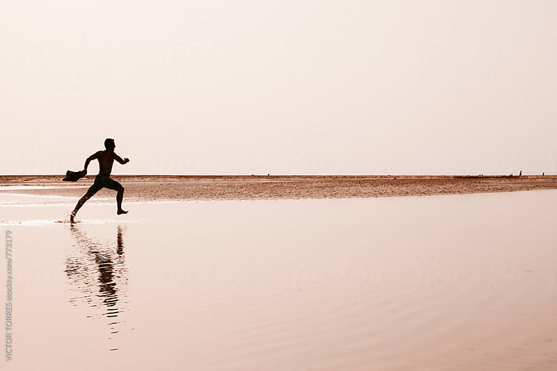 Man Running Over a Sea Puddle by VICTOR TORRES for Stocksy United