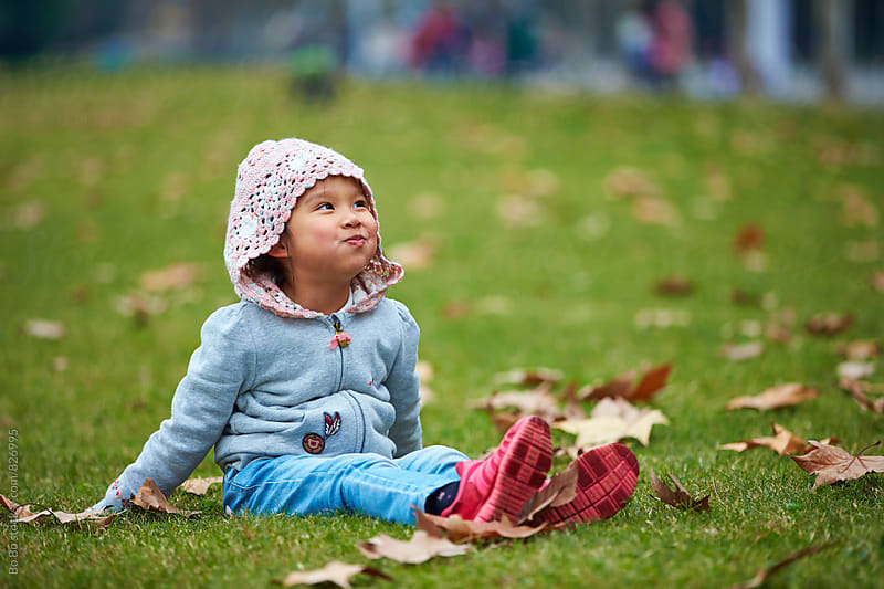little Chinese girl outdoor in the park at autumn time by Bo Bo for Stocksy United