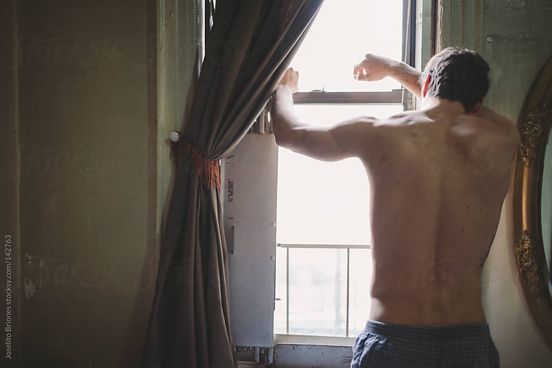 Shirtless Man in Boxer Shorts Looking Out the Window by Joselito Briones for Stocksy United