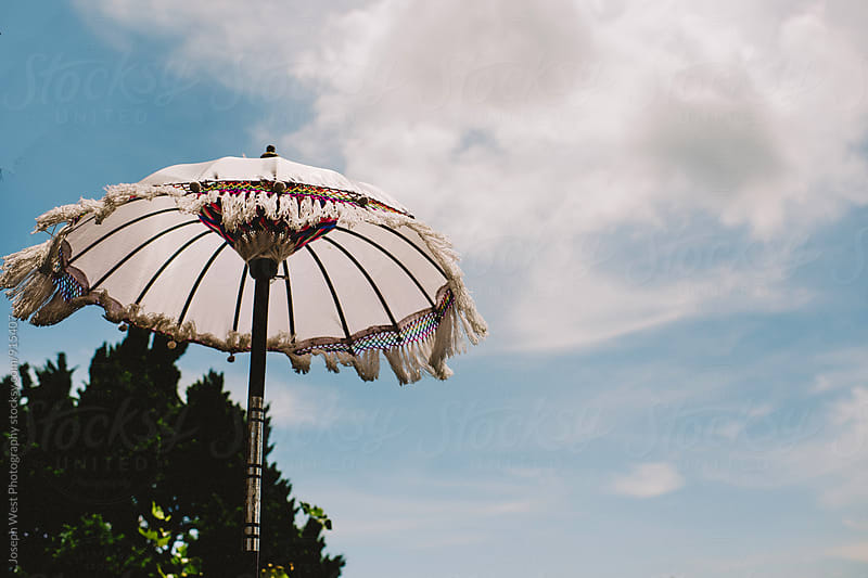An umbrella against the sky by Joseph West Photography for Stocksy United