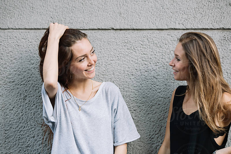 Two young women smiling against the wall by Alberto Bogo for Stocksy United