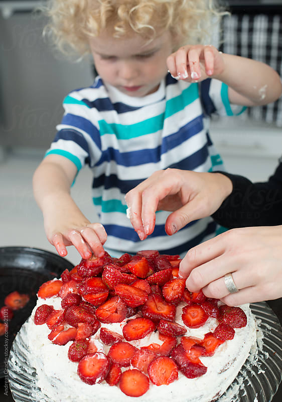 a young family baking a birthday cake by Andreas Gradin for Stocksy United