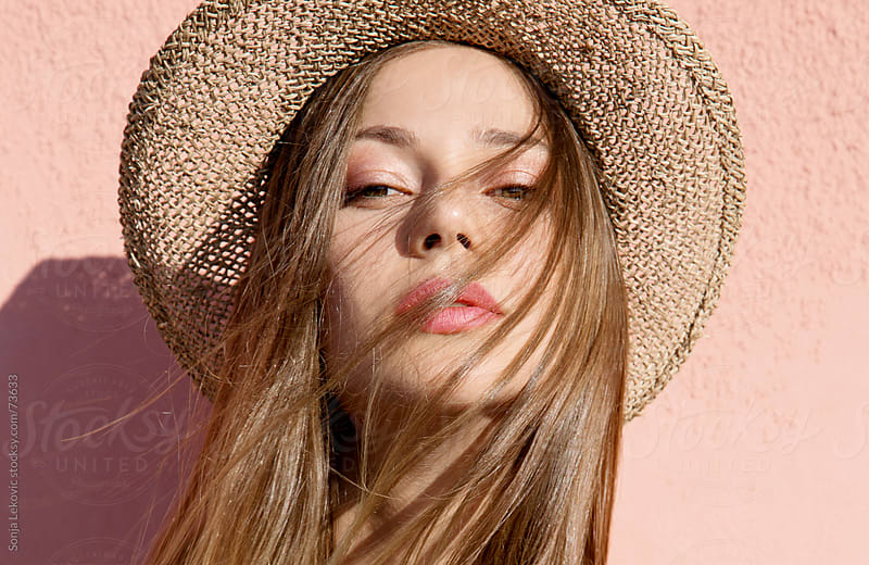 summer beauty with a hat on pink background by Sonja Lekovic for Stocksy United