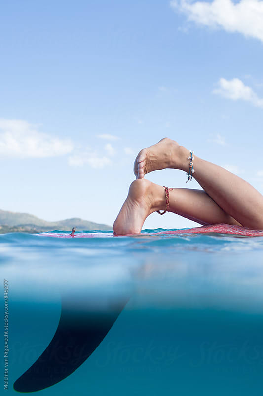 Close up of feet with anklets on a surfboard  by MELCHIOR / PHOTOGRAPHER for Stocksy United