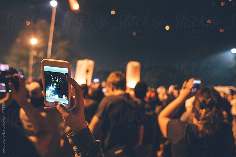 Festival time - People taking photos on phone of fire lanterns flying in the night sky by Jovo Jovanovic for Stocksy United